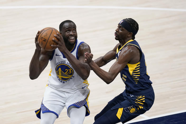 Golden State Warriors' Draymond Green (23) goes to the basket against Indiana Pacers' Justin Holiday during the second half of an NBA basketball game Wednesday, Feb. 24, 2021, in Indianapolis. (AP Photo/Darron Cummings)