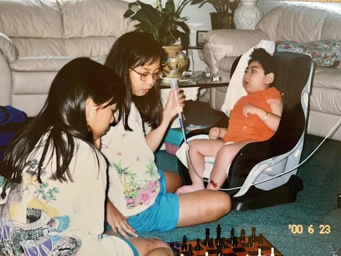 Jennifer and Jessica Pham play a game of chess while watching over their brother, Justin Nguyen. The sisters, 6 and 7 when Justin was born, are now in their early 30s and remain devoted to his care.