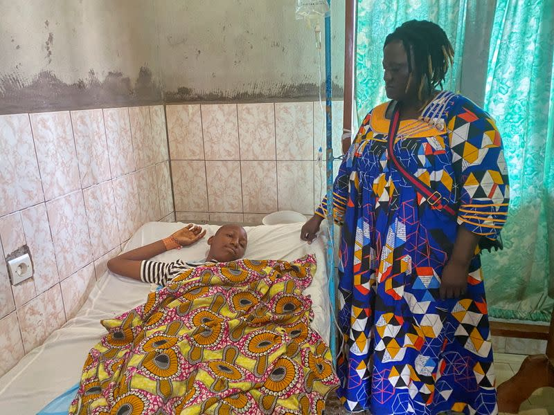 Edwin Ojong Ayuk Mbeng stands beside her son Blessing Mbeng, 13, who was shot by gunmen after they stormed his school, as he lies in a hospital bed in Kumba