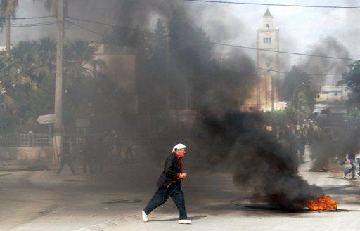A Tunisian man walks past burning tyres during a demonstration in Kasserine in western Tunisia on October 22, 2012