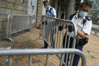 """Police set up barriers, Friday, July 30, 2021, as they wait for Tong Ying-kit to arrives at a court in Hong Kong for his sentencing for the violation of a security law for carrying a flag reading """"Liberate Hong Kong, Revolution of our times"""" during a 2020 protest. Tong has been sentenced to nine years in prison in the closely watched first case under Hong Kong's national security law as Beijing tightens control over the territory. (AP Photo Vincent Yu)"""