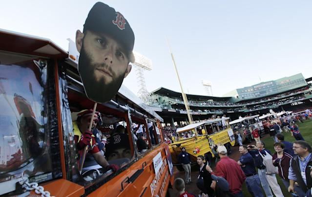 A giant head photograph of Boston Red Sox's Dustin Pedroia is held out of a duck boat at Fenway Park as they prepare to leave for a parade in celebration of the baseball team's World Series win, Saturday, Nov. 2, 2013, in Boston. (AP Photo/Charles Krupa)