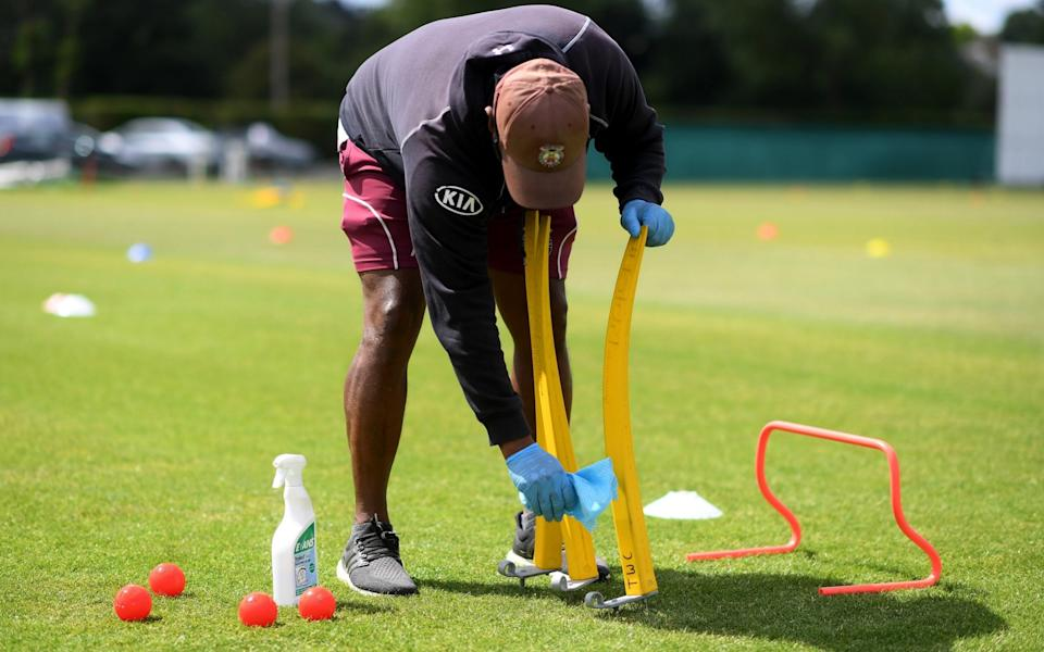 A cricket coach cleans equipment during a junior training session - GETTY IMAGES