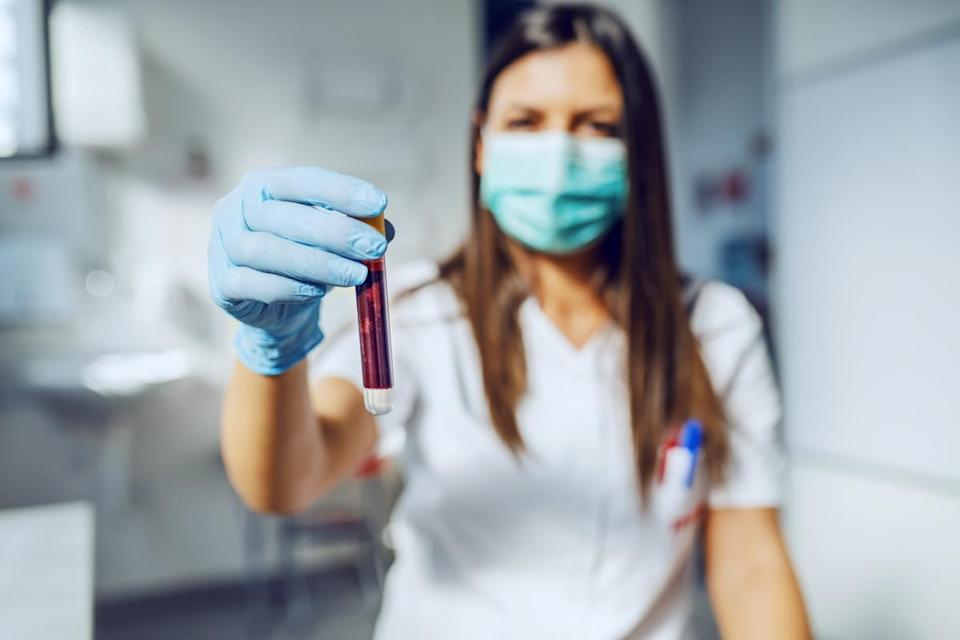 lab assistant holding test tube with blood while standing in