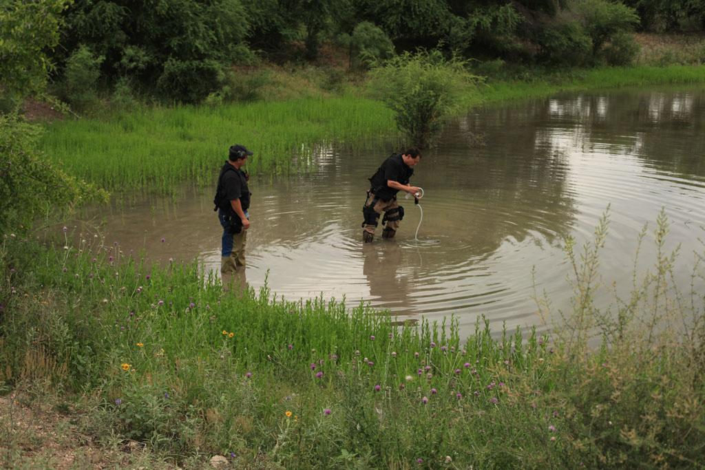 Houston, TX, USA - Steven Vanase and Dr. Tom Perez check a local water source for contamination.
