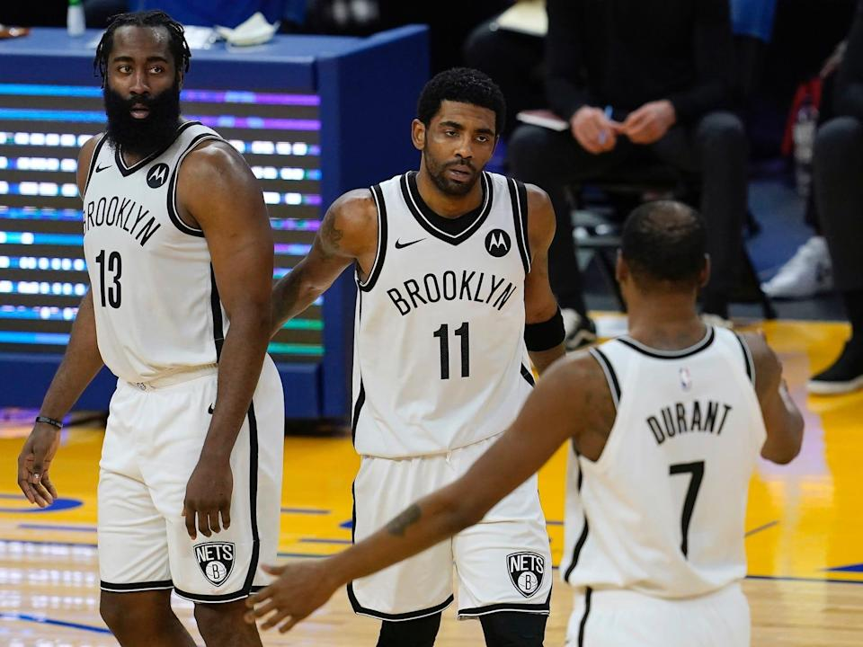 James Harden, Kyrie Irving, and Kevin Durant high-five during a game.
