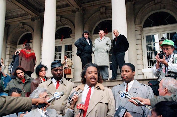 The Rev. Al Sharpton, center, is flanked by Dr. Elgin Watkins, left, and Eric Adams, President of the Police Guardians Association at a news conference at City Hall in New York, Dec. 9, 1993.