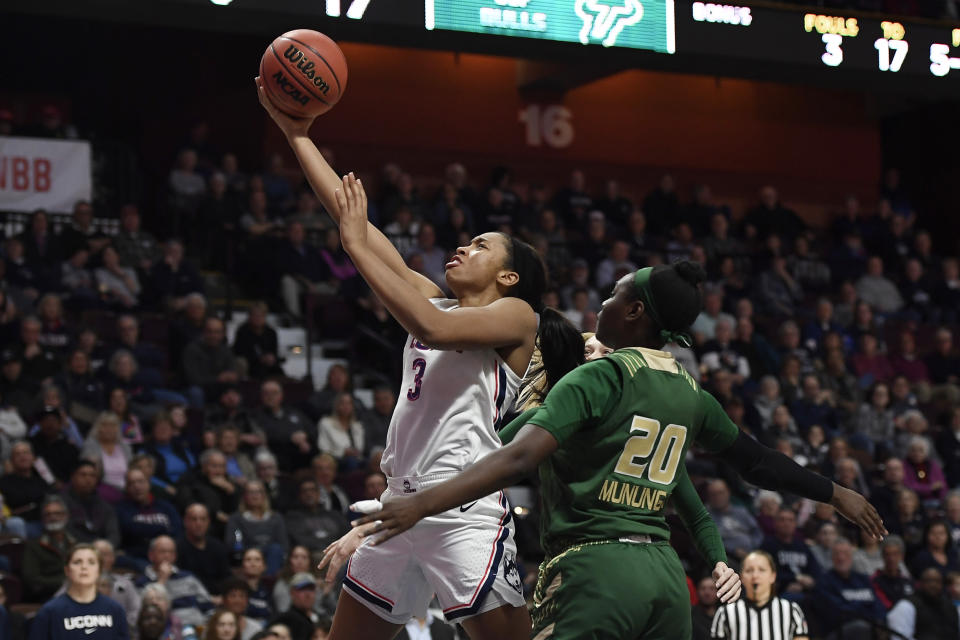 Connecticut's Megan Walker (3) goes up to the basket as South Florida's Bethy Mununga (20) defends during the second half of an NCAA college basketball game in the American Athletic Conference tournament semifinals at Mohegan Sun Arena, Sunday, March 8, 2020, in Uncasville, Conn. (AP Photo/Jessica Hill)