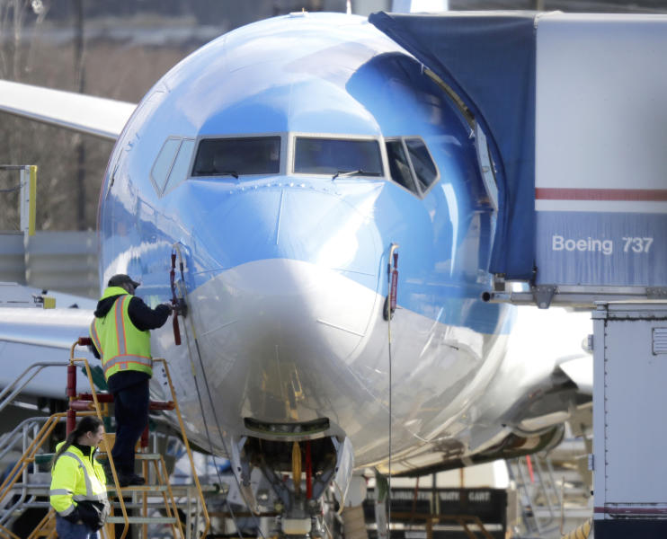 FILE- In this March 13, 2019, file photo a worker stands on a platform near a Boeing 737 MAX 8 airplane being built for TUI Group at Boeing Co.'s Renton Assembly Plant in Renton, Wash. Boeing is cutting production of its grounded Max airliner this month to focus on fixing flight-control software and getting the planes back in the air. The company said Friday, April 5, that starting in mid-April it will cut production of the 737 Max from 52 to 42 planes per month. (AP Photo/Ted S. Warren, File)