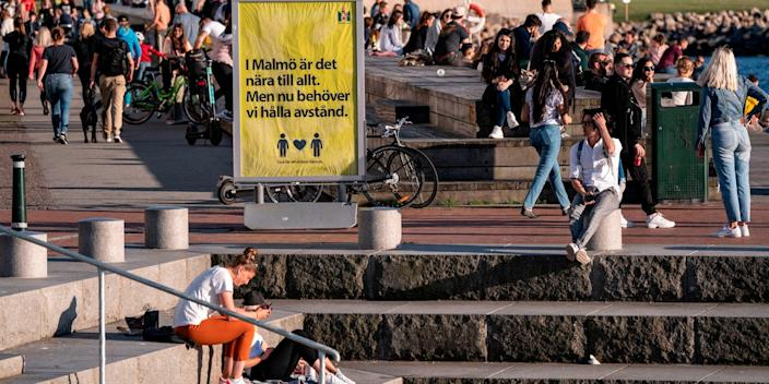People sit outside in Malmo, Sweden, in May 2020 by a sign that urges people to keep their distance during the coronavirus pandemic.