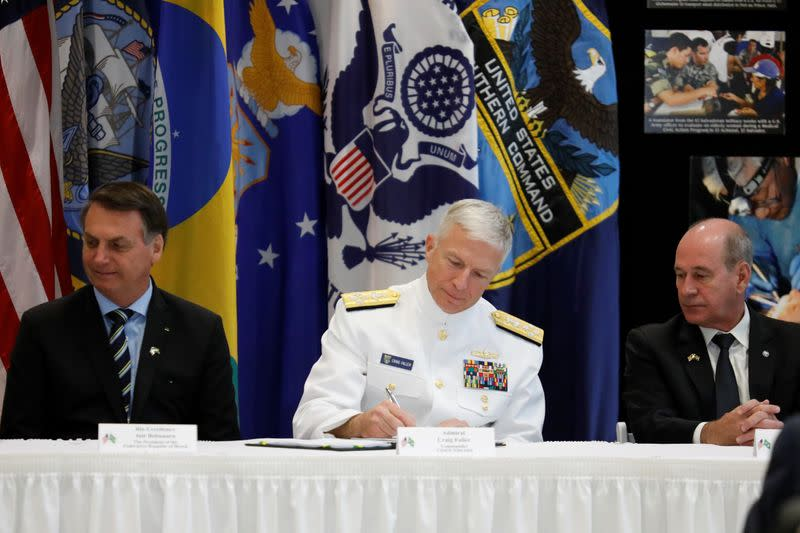 Commander of the U.S. Southern Command Admiral Craig S. Faller signs a document during an agreement signing ceremony, in Miami