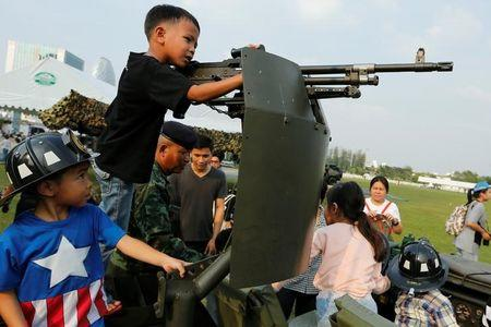 Children play with a weapon on the top of an army vehicle during Children's Day celebration at a military facility in Bangkok, Thailand January 14, 2017. REUTERS/Jorge Silva