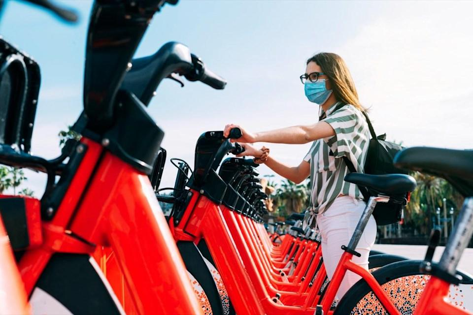 Woman wearing protective face mask taking a rented electric bicycle