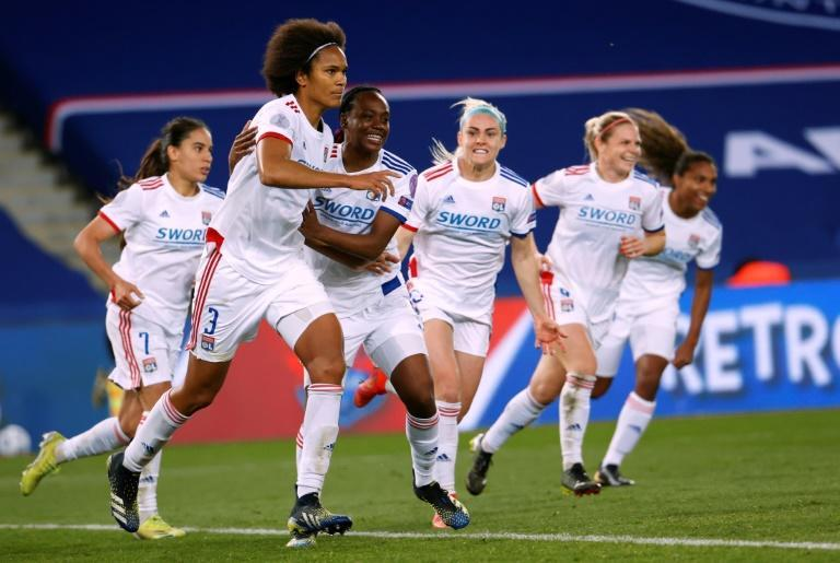 Lyon players rush to celebrate with Wendie Renard after her winning penalty against Paris Saint-Germain