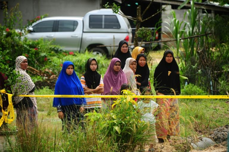 Residents of Khoksator village in southern Thailand watch the police investigate a deadly shooting, on March 2, 2017