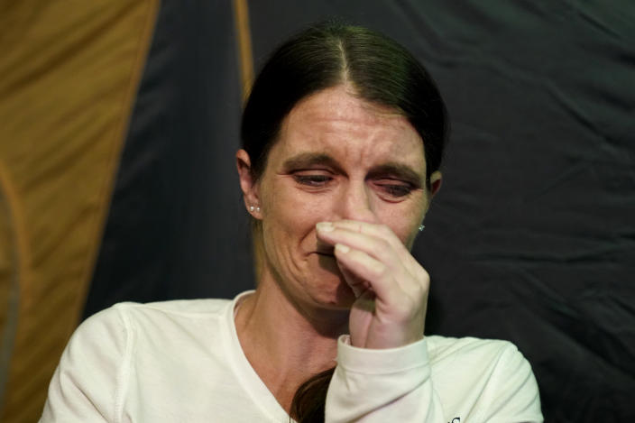 CORRECTS SPELLING TO CRISTIN, INSTEAD OF CRISTEN - Cristin Trahan cries inside a tent where she now lives with her husband, where their home once stood, in the aftermath of Hurricane Laura and Hurricane Delta, in Lake Charles, La., Friday, Dec. 4, 2020. (AP Photo/Gerald Herbert)