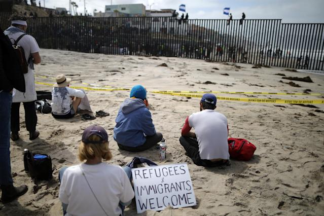 <p>Supporters sit on the U.S. side of the U.S.-Mexico border wall at Border Field State Park as members of a migrant caravan from Central America stand on the other side, in San Diego, California, April 29, 2018. (Photo: Lucy Nicholson/Reuters) </p>