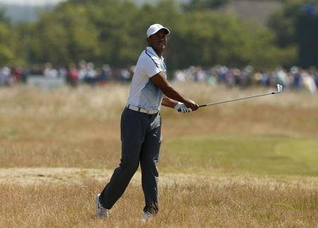 Tiger Woods of the U.S. watches his second shot on the 17th hole during the first round of the British Open Championship at the Royal Liverpool Golf Club in Hoylake, northern England July 17, 2014. REUTERS/Cathal McNaughton