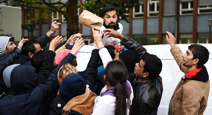 A vonlunteer hands over care bags to refugees at at an asylum seeker registration office in Berlin on September 7, 2015 (AFP Photo/Tobias Schwarz)