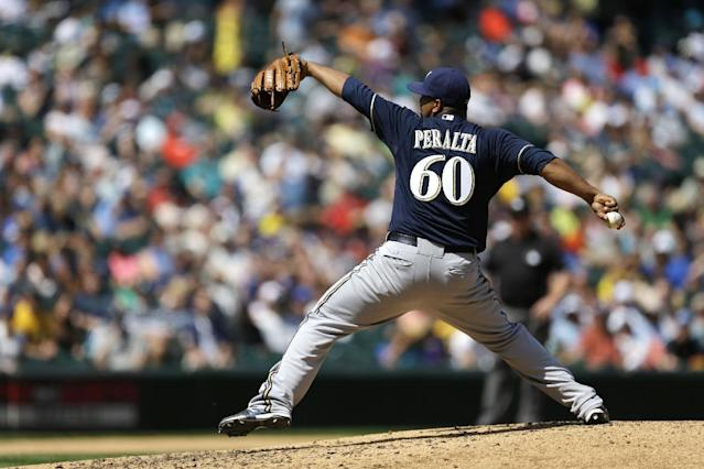 Milwaukee Brewers starting pitcher Wily Peralta throws in the fifth inning of a baseball game against the Seattle Mariners, Sunday, Aug. 11, 2013, in Seattle. (AP Photo/Ted S. Warren)