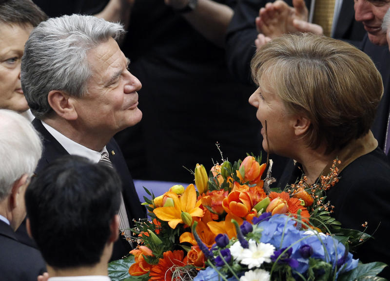 German Chancellor Angela Merkel, right, hands over a bunch of flowers to new elected German President Joachim Gauck, left, at the parliament building Reichstag in Berlin, Germany, Sunday, March 18, 2012. (AP Photo/Michael Sohn)