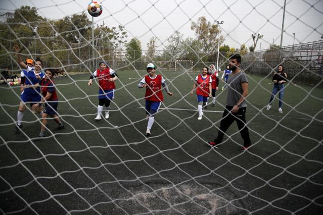 In this Wednesday, April 24, 2019 photo, members of Hestia FC Women's Refugee Soccer team practise during a training session in Athens. Many of the players at Hestia FC weren't allowed to play or even watch soccer matches in their home countries. Hestia FC was set up by the Olympic Truce Centre, a non-government organization created in 2000 by the International Olympic Committee and Greek Foreign Ministry. (AP Photo/Thanassis Stavrakis)