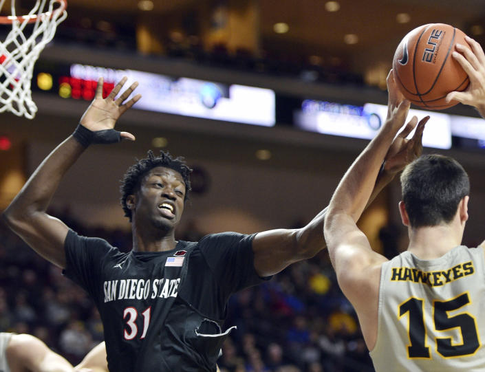 San Diego State forward Nathan Mensah (31) defends against Iowa forward Ryan Kriener (15) during the second half of an NCAA college basketball game Friday, Nov. 29, 2019, in Las Vegas. San Diego State was three days away from finding out whether it would be a No. 1 or 2 seed in the NCAA Tournament when March Madness was canceled because of the coronavirus pandemic. Their season ended before they could find out how truly historic it could have been. They finished 30-2, ranked No. 6 and with a Mountain West Conference regular-season championship banner hanging in Viejas Arena. (AP Photo/David Becker, File)