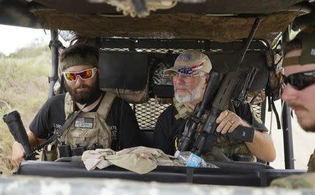 "Members of the ""Patriots"" Huggie Bear (L, not his real name), Ray (C, no last name given) and Will (R, no last name given) patrol in their UTV near a camp of patriots near the U.S.-Mexico border outside Brownsville, Texas September 2, 2014. REUTERS/Rick Wilking"