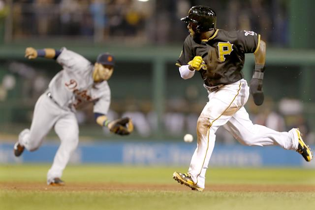 Pittsburgh Pirates' Josh Harrison, right, heads for third as Detroit Tigers shortstop Eugenio Suarez fields a ground ball by Jordy Mercer who was out on the fielders choice in the fifth inning of the baseball game on Tuesday, Aug. 12, 2014, in Pittsburgh. (AP Photo/Keith Srakocic)