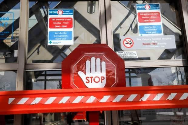 An entrance to the Peter Lougheed Centre hospital in Calgary was blocked off in April 2020, to screen essential visitors for COVID-19. Doctors and scientists say the virus is now spreading faster in Alberta than during the pandemic's third wave. (Jeff McIntosh/The Canadian Press - image credit)