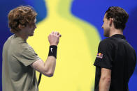 Andrey Rublev of Russia, left,celebrates defeating Dominic Thiem of Austria, right, at the ATP World Finals tennis tournament at the O2 arena in London, Thursday, Nov. 19, 2020. (AP Photo/Frank Augstein)
