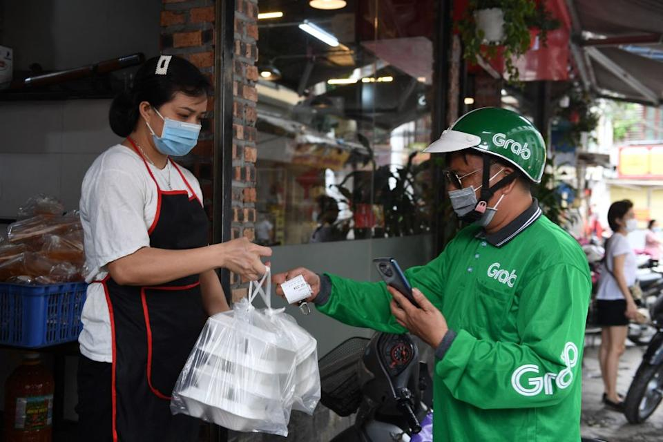 A delivery driver receives a take away food order in Hanoi on May 25, 2021 as city authorities expanded closure orders. Source: Getty