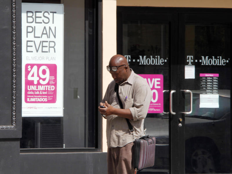 A man checks his mobile phone as he walks past a T-Mobile store in downtown Los Angeles, California August 31, 2011. The Obama administration on Wednesday fired a legal broadside to block AT&T Inc's $39 billion acquisition of T-Mobile, launching its biggest challenge yet to a takeover and dealing the carrier a potentially costly blow. REUTERS/Fred Prouser (UNITED STATES - Tags: BUSINESS TELECOMS)