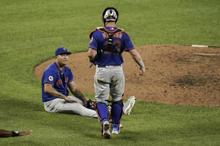 New York Mets starting pitcher Taijuan Walker, bottom, sits in front of the pitching mound after he stopped a sharp line drive by Baltimore Orioles' DJ Stewart and threw hime out at first base during the eighth inning of a baseball game, Wednesday, June 9, 2021, in Baltimore. Mets' catcher James McCann approaches him to check on him. Walker stayed in the game. (AP Photo/Julio Cortez)