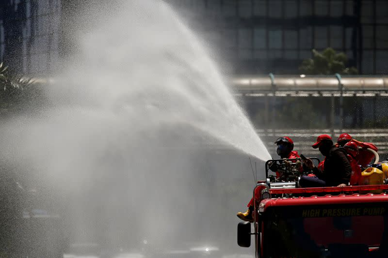 Firefighters spray disinfectant using high pressure pump truck to prevent the spread of coronavirus disease (COVID-19), on the main road in Jakarta