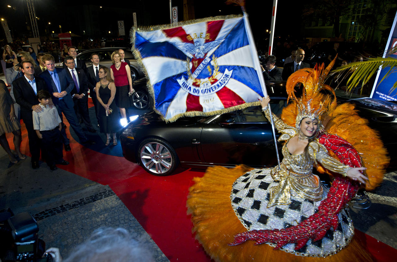 Britain's Prince Harry, background left, in blue tie, watches a samba dance presentation in Rio de Janeiro, Brazil, Friday March 9, 2012. Harry is in Brazil at the request of the British government on a trip to promote ties and emphasize the transition from the upcoming 2012 London Games to the 2016 Olympics in Rio de Janeiro. (AP Photo/Victor R. Caivano)