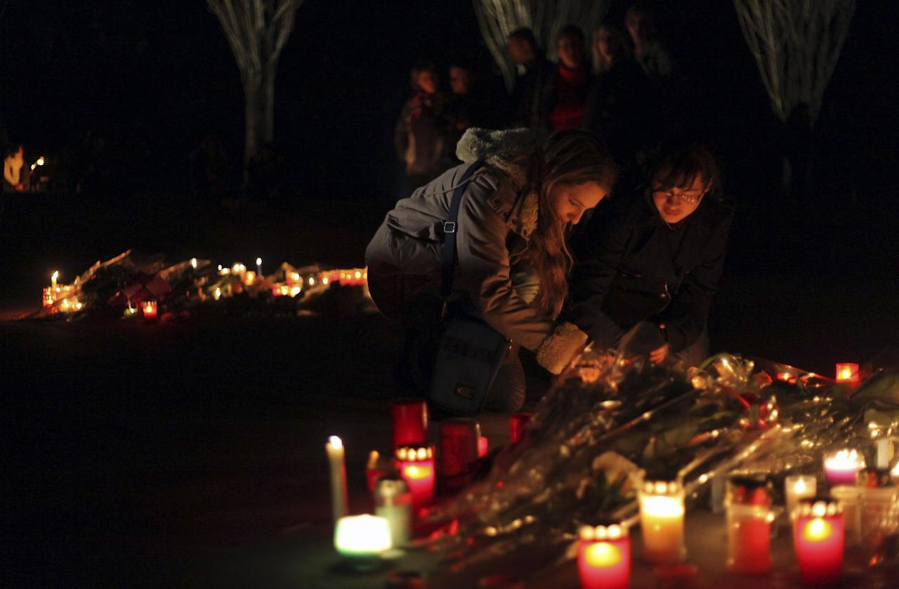 Unidentified people light candle tributes during a White March in homage to the victims of a tourist bus crash in a tunnel of the motorway A9, in Sierre, western Switzerland, Wednesday, March 14, 2012. Twenty-eight people, including 22 children, returning to Belgium from a skiing holiday died in the bus accident late Tuesday, and another 24 children are hospitalized, Swiss police said Wednesday. Belgium flew anxious parents and relatives to the scene Wednesday. (AP Photo/KEYSTONE, Maxime Schmid)