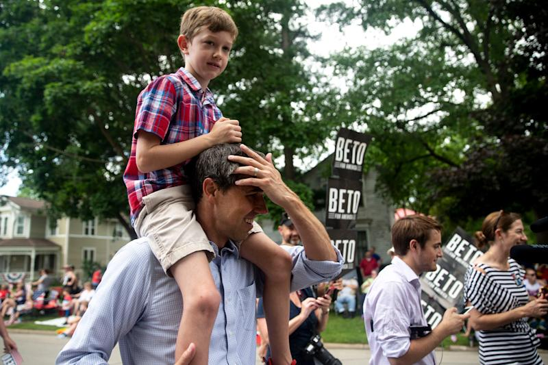 Sen. Beto O'Rourke, D-Texas, walks in the Independence Fourth of July parade with his son Henry, 8, on his shoulders on July 4, 2019, in Independence, Iowa.