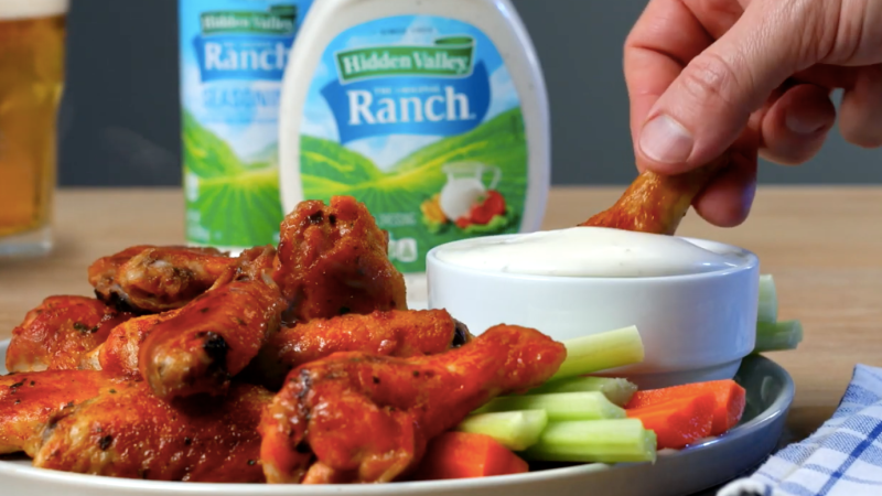 Hand dips buffalo chicken wing into bowl of ranch dressing