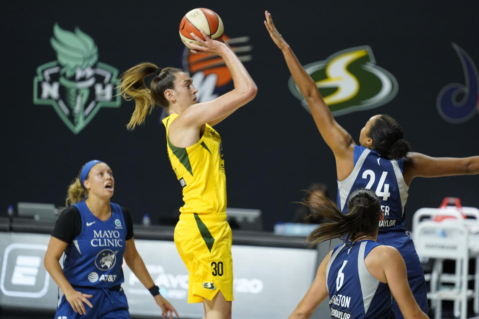 Breanna Stewart in a yellow jersey jumps up.