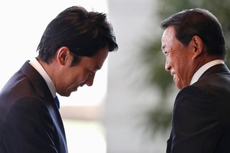 Japan's new Environment Minister Shinjiro Koizumi reacts next to Deputy Prime Minister and Finance Minister Taro Aso, as he arrives at Prime Minister Shinzo Abe's official residence in Tokyo