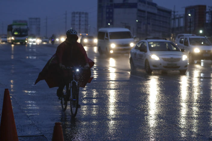 A man ina. raincoat rides his bicycle during heavy rains from Typhoon Vamco in Quezon city, Philippines on Wednesday, Nov. 11, 2020. Typhoon Vamco blew closer Wednesday to a northeastern Philippine region still struggling to recover from a powerful storm that left a trail of death and destruction just over a week ago, officials said, adding that thousands of villagers were being evacuated again to safety. (AP Photo/Aaron Favila)