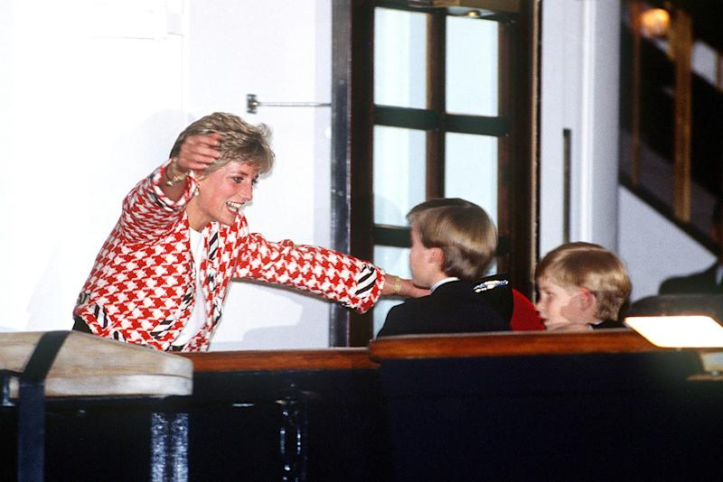 On the royal tour of Canada, Princess Diana goes in for the hug with Prince William and Prince Harry. They're on the deck of the Britannia in Toronto.