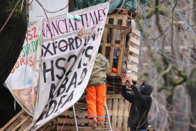A HS2 protester catches a food parcel that has been given to him in trees at the encampment in Euston Square Gardens