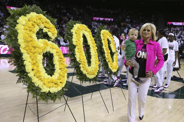 Baylor head coach Kim Mulkey holds her grandson Kannon Reid Fuller as she is congratulated for her 600 wins before an NCAA college basketball game against Oklahoma, Saturday, Feb. 22, 2020, in Waco, Texas. (AP Photo/ Jerry Larson)