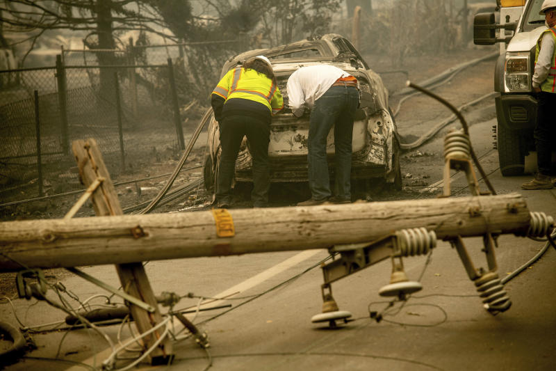 FILE - In this Nov. 10, 2018 file photo, with a downed power utility pole in the foreground, Eric England, right, searches through a friend's vehicle after the wildfire burned through Paradise, Calif.  Pacific Gas & Electric has agreed to pay $11 billion to a group of insurance companies representing most of the claims from Northern California wildfires in 2017 and 2018 as the company tries to emerge from bankruptcy, the utility announced Friday, Sept. 13, 2019. (AP Photo/Noah Berger, File)