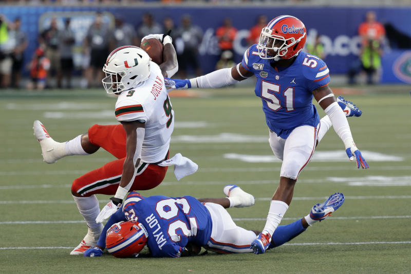 Miami tight end Brevin Jordan, left, is brought down by Florida defensive back Jeawon Taylor (29) and linebacker Ventrell Miller (51) after a short gain during the first half of an NCAA college football game Saturday, Aug. 24, 2019, in Orlando, Fla. (AP Photo/John Raoux)