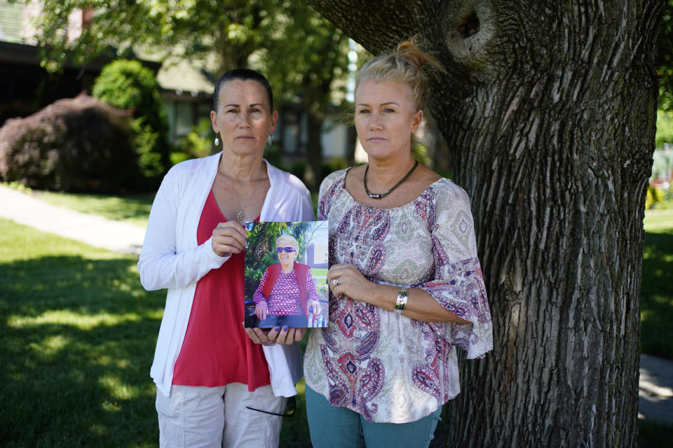 """Angela Ermold, right, and her sister, Denise Gracely, pose with a photo of their mother, Marian Rauenzahn, Thursday, June 17, 2021, in Fleetwood, Pa. Pandemic restrictions are falling away almost everywhere — except inside many of America's nursing homes. """"They have protected them to death,"""" said Gracely. (AP Photo/Matt Slocum)"""