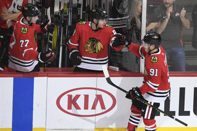 Chicago Blackhawks' Drake Caggiula (91) celebrates with teammates Patrick Kane (88) and Kirby Dach (77) on the bench after scoring a goal during the second period of an NHL hockey game against the Washington Capitals, Sunday, Oct. 20, 2019, in Chicago. (AP Photo/Paul Beaty)