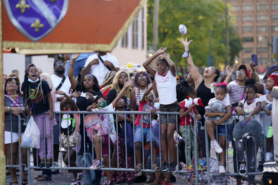 """Parade-goers vie for throws during a parade dubbed """"Tardy Gras,"""" to compensate for a cancelled Mardi Gras due to the COVID-19 pandemic, in Mobile, Ala., Friday, May 21, 2021. (AP Photo/Gerald Herbert)"""
